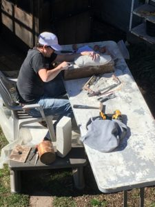 A block of plaster, a pile of tools and an artist carving a cicada.